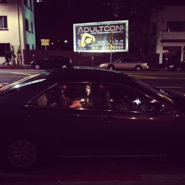 2 chicks getting picked up by their parents in front of a sweet-ass Adultcon billboard.  The mom waved to me.